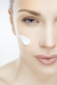 Close-up of a beautiful woman with cream on her face